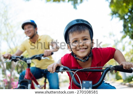 Little boy in helmet enjoying riding a bicycle