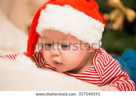 little boy in holiday hat on a bed at christmas tree background