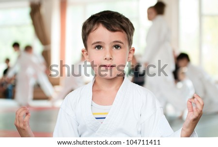 Little boy in kimono meditation before aikido competition in sport hall - stock photo