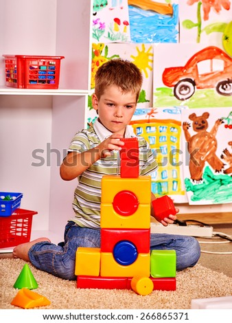 Little boy  in kindergarten stacking block. Painting  background. - stock photo