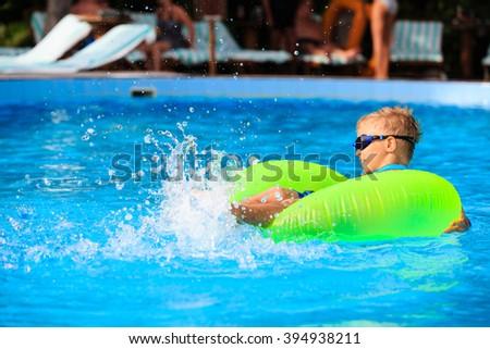 little boy in life ring having fun at swimming pool - stock photo