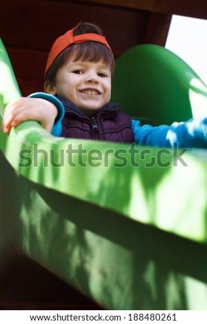 Little boy in orange cap on slide, teeth smile - stock photo