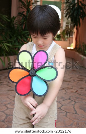 Little boy in overalls playing with windmill - stock photo