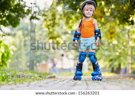 Little boy in protective equipment and rollers stands on walkway in park, low angle view - stock photo