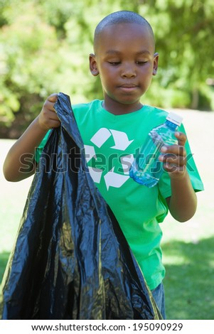 Little boy in recycling tshirt picking up trash on a sunny day - stock photo