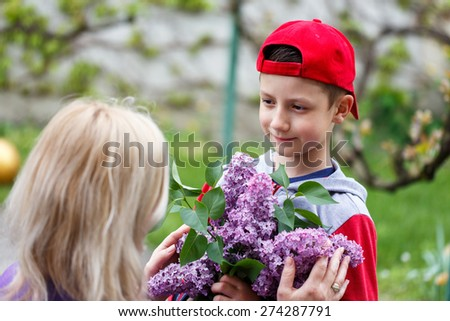 Little boy in red cap give lilac to mom, mother's day - stock photo