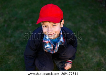 Little boy in red cap squat outdoor in meadow - stock photo