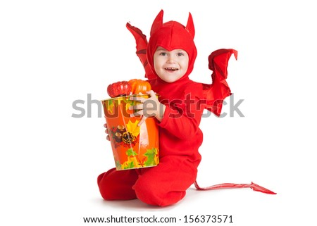 little boy in red devil costume sitting with big bucket with pumpkins over white background - stock photo