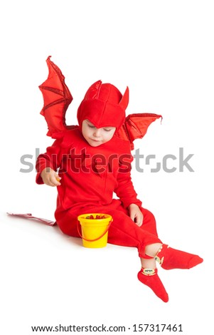 little boy in red devil costume sitting with bucket over white background - stock photo