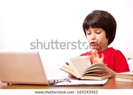 little boy in red t-shirt with computer and textbooks on white background