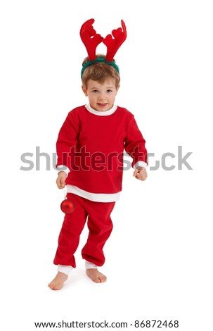 Little boy in reindeer hair band wearing santa costume playing with christmas bulb.? - stock photo