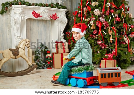 Little boy in Santa cap sits on toy plastic steam engine at room decorated to Christmas celebration - stock photo