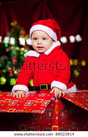 Little boy in Santa clothing standing in a large red present box - stock photo