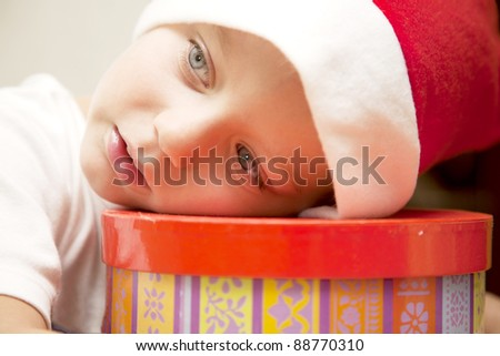 little boy in santa costume dream about gift on gift box - stock photo