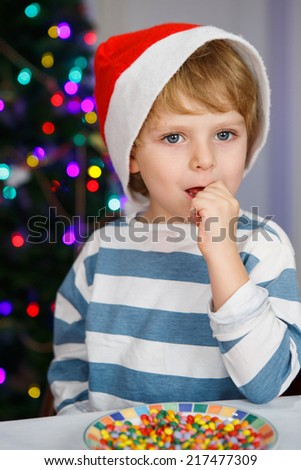 Little boy in santa hat with christmas tree and lights on background eating sweets - stock photo