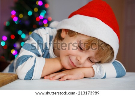 Little boy in santa hat with christmas tree and lights on background, sleeping and dreaming - stock photo