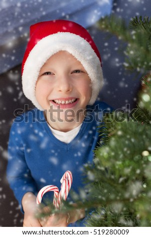 little boy in santa's hat holding candy canes enjoying snowy christmas time