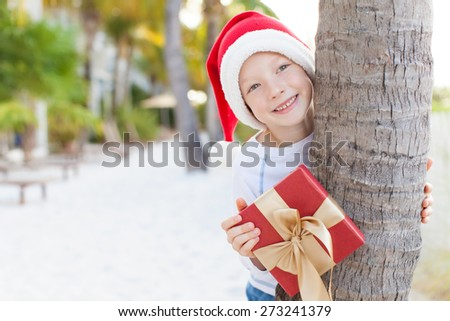 little boy in santa's hat with wrapped present at the tropical beach, christmas vacation concept - stock photo