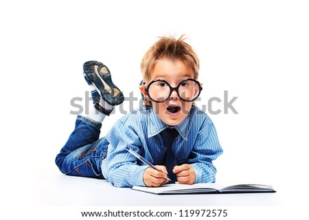 Little boy in spectacles and suit lying on a floor with a diary. Isolated over white background. - stock photo