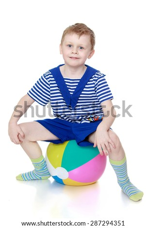Little boy in striped the clothes of a sailor sitting on a big inflatable ball-Isolated on white background - stock photo