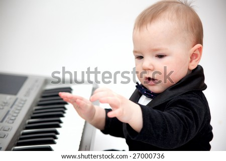 little boy in tailcoat playing piano - stock photo
