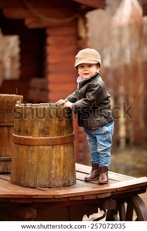 little boy in the cap and a brown leather jacket standing on the table near the  barrel in the garden in spring or autumn - stock photo