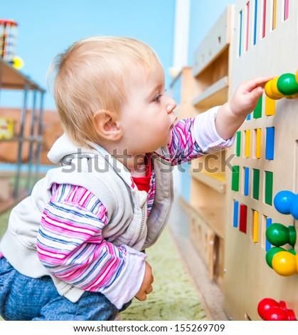 little boy in the classroom early development plays with numerous bright toys - stock photo