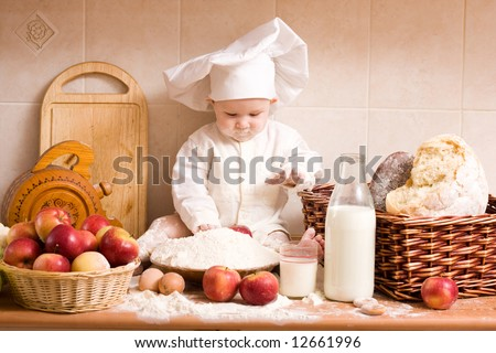 little boy in the cook costume at the kitchen - stock photo