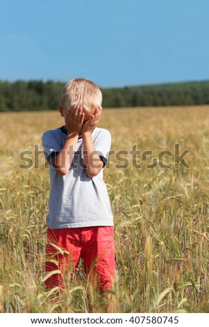 Little boy in the field of wheat in the sunny summer day - stock photo