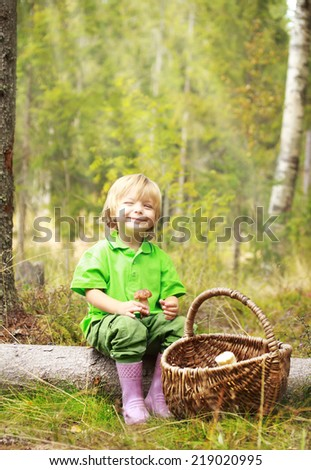 Little boy in the forest with straw basket of mushrooms. - stock photo