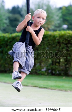 Little boy in the playground with a cable-way - stock photo