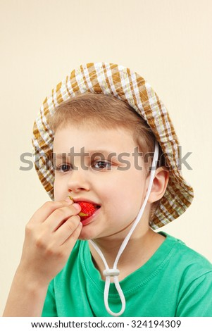 Little boy in the summer hat eating a fresh ripe strawberry