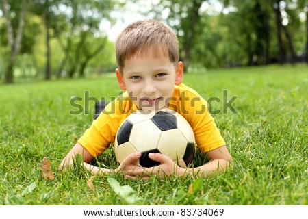 Little boy in the summer park with a ball - stock photo