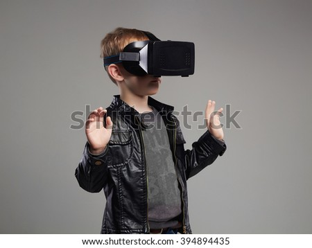 little Boy in virtual reality glasses playing the game. 3D VR glasses cardboard