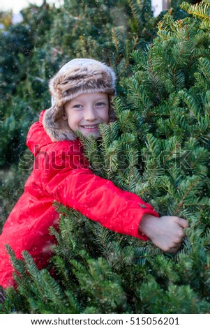 little boy in warm clothes buying christmas tree at snowy weather, holiday concept