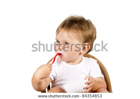Little boy in white eating with a red spoon. Isolated over white background.