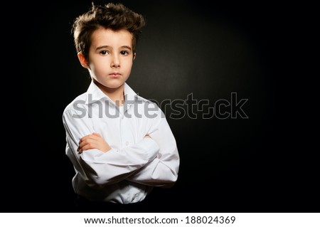 Little boy in white shirt portrait in low key with arms crossed - stock photo