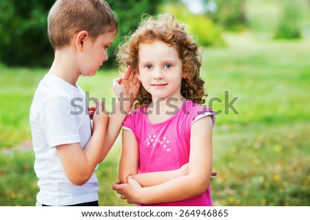 Little boy in white t-shirt whispers a girl in red dress. - stock photo