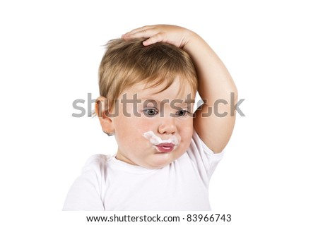 Little boy in white with milky face and his hand on his head. Isolated on white.