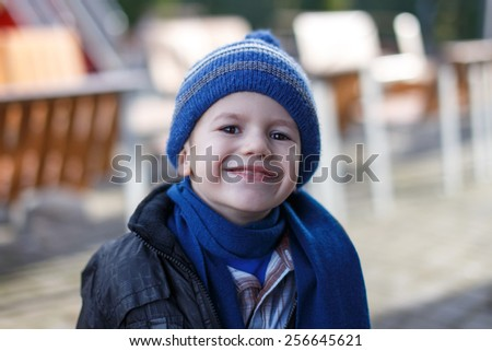 Little boy in winter cap and scarf, outdoor portrait - stock photo