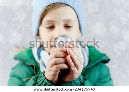 little boy in winter clothes with small snow globe - stock photo
