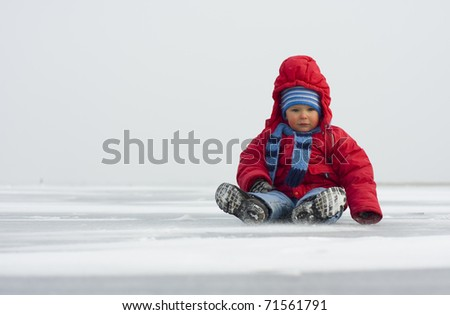 Little boy in winter on ice - stock photo