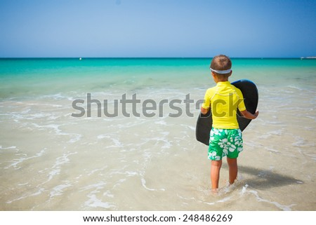 Little boy in yellow has fun surfing - stock photo
