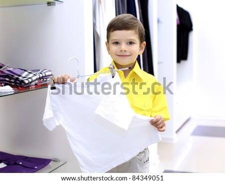 Little boy in yellow shirt doing shopping - stock photo