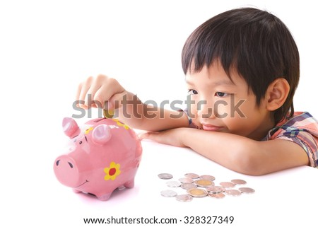 Little boy insert coin into piggy bank on white background - stock photo