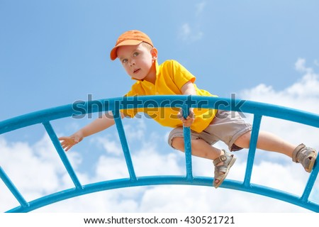 little boy is afraid of heights. Fear of heights. cautious child climbs up the ladder on the playground. copy space for your text - stock photo