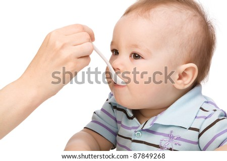 Little boy is being feed by his mother, isolated over white