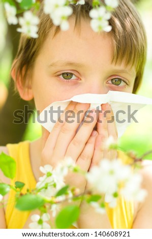 Little boy is blowing his nose outdoors - stock photo