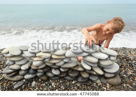 little boy is building construction of many pebbles on a sea coast near water. - stock photo