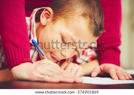 Little boy is doing his homework for elementary school. - stock photo